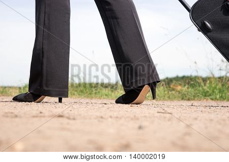 Woman walking on the dirt road with hand luggage suitcase