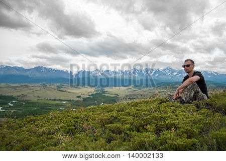 male traveler  sitting on the grass on a background of mountains