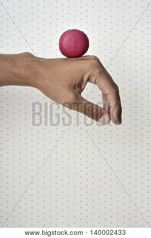 closeup of a red macaron on the back of the hand of a young caucasian man, against a dot-patterned background