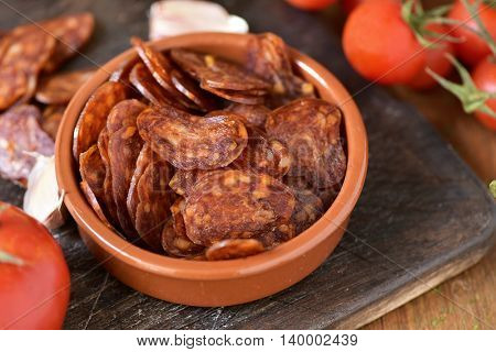 closeup of an earthenware bowl with some slices of Spanish chorizo, a pork sausage typical of Spain, on a rustic wooden table with some tomatoes and garlic cloves