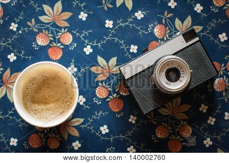old vintage camera with a cup of coffee on vintage fabric background.