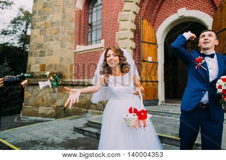 Jubilant bride and groom leaving the church after a wedding ceremony.