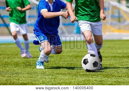 Young boys kicking soccer football on the sports field. Youth blue and green teams tournament competition