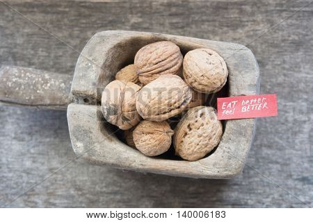 Eat Better Feel Better - text and walnuts on a rustic wooden table