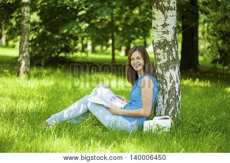 Young beautiful brunette woman reading a womens magazine sitting on the green grass in the summer park