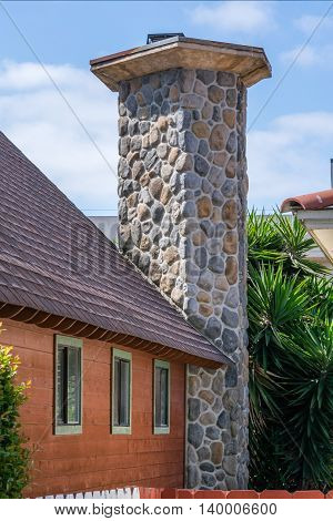 rustic wooden cottage with massive stone chimney