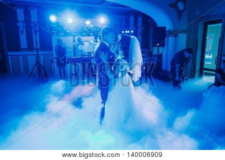 Wedding dance of just married couple. The hall is covered with white fume and filled by blue lights.
