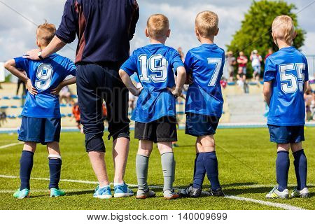 Football soccer match game for children. Youth sports team with soccer coach during football match at the stadium. Kids reserve players waiting on a bench with coach and watching soccer match.