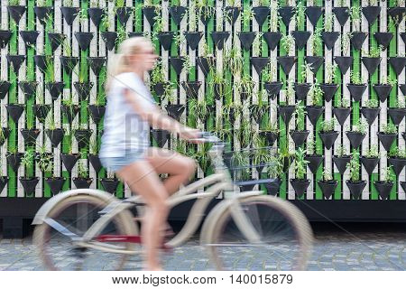 Motion blure of woman riding bycicle by green urban vertical garden wall in Ljubljana, European green capital of Europe 2016. Sustainable green city concept. poster
