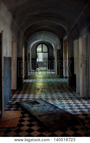 Abstract image of a dark spooky corridor in an old abandoned hospital buiding with shatter on the checkered floor