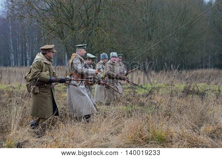 GATCHINA, RUSSIA - NOVEMBER 07, 2015: The officer with the soldiers of the white guard army of general Yudenich are put forward on the line of attack. International military-historical festival