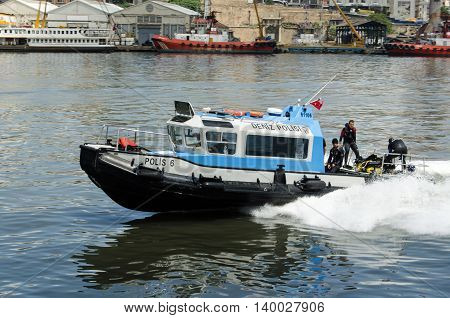 ISTANBUL TURKEY - JUNE 5 2016: Police divers on a boat travelling rapidly up the Golden Horn passing the Beyoglu district of Istanbul Turkey.