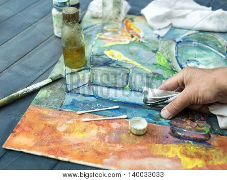 Artist hand with cloth demonstrating a painting technique. Outdoor selective focus shot