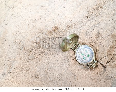 A compass laid on the sand overhead shot concept of the way lost
