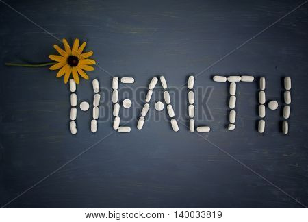 A word Health written with pills and yellow flower overhead filtered studio shot concept of health care
