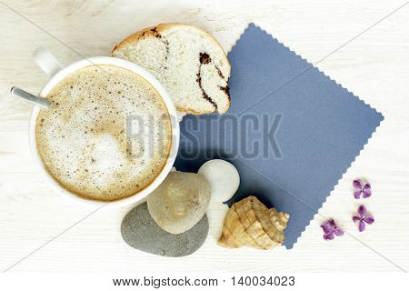 frothy cappuccino with pastries on the background of cards for wishes and sea stones with flowers top view / sea fantasy coffee with a dolphin