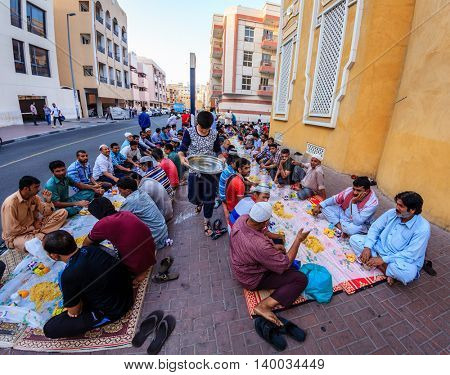 Dubai, June 14, 2016: men are gathered for iftar dinner near a mosque in Bur Dubai, UAE