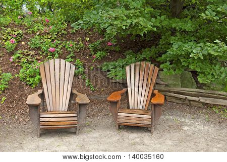 Two inviting wooden lawn chairs in the garden