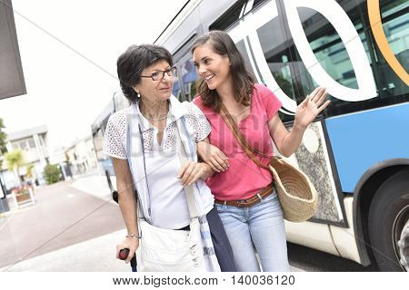 Senior woman with home carer getting off the bus