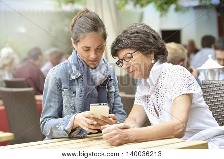 Senior woman and home carer at caf�½ terrace using smartphone