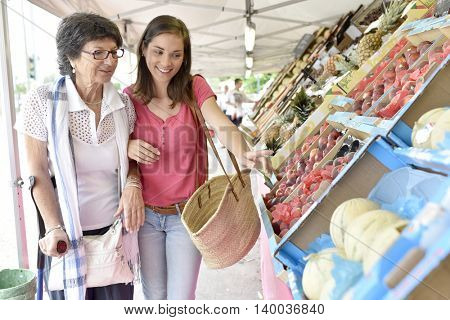 Senior woman going to grocery store with help of carer