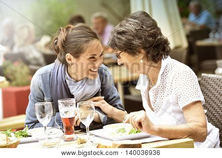 Senior woman with home carer having lunch at restaurant