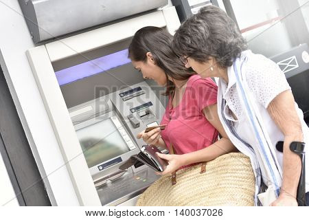 Home carer and disabled woman getting cash from bank