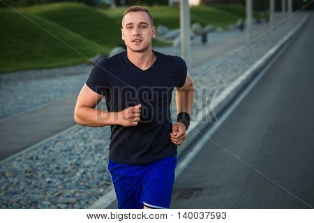 Close-up portrait of athletic man running on the road, muscular build young runner working out while jogging in the park. Evening