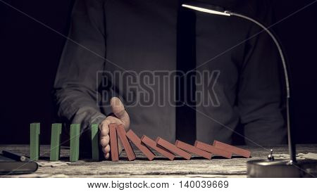Conceptual image of the Domino Effect with a row of red dominoes falling intercepted by a mans hand preventing the chain reaction with green upright dominoes following on close up view by lamp light.