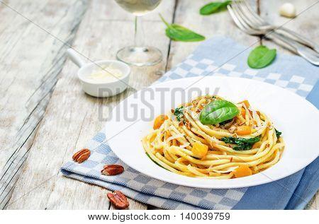 pumpkin spinach pecan pasta on light wooden background
