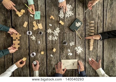 Business planning and brainstorming concept with a team of ten businessmen organizing strategy while holding puzzle pieces writing down ideas on paper and rearranging wooden blocks top view.