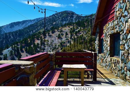 Rustic lodge with an outdoor furnished patio with hanging lights, chairs, and tables overlooking rugged mountains taken in Mt Baldy, CA