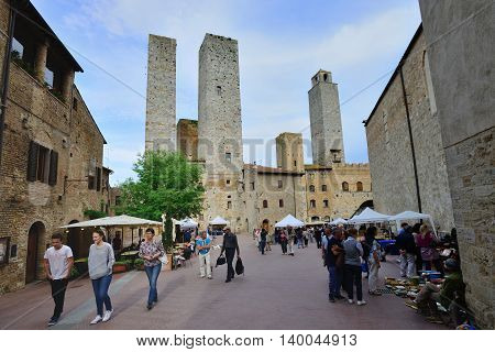 SAN GIMIGNANO, ITALY - APRIL 28: Tourists walk in San Gimignano, Italy, April 28, 2013. The Historic Center of San Gimignano is a UNESCO World Heritage Site.