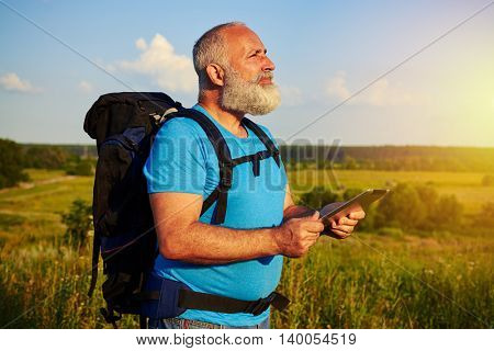 Fit aged male in casual clothes with rucksack behind his back is holding a data tablet and looking into the distance in the field