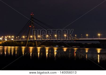 Night bridge with lights reflecting in river waters