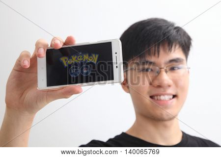 Kuala Lumpur,Malaysia 23th July 2016,teenager holding a smartphone with pokemon go logo on the screen