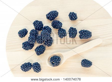 Blackberries on wooden background with wooden spoon