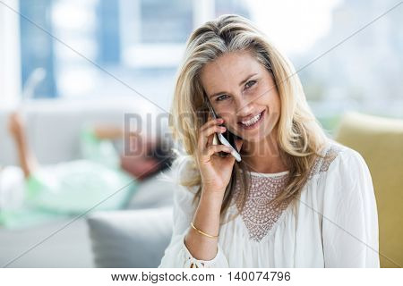 Portrait smiling woman using mobile phone while man in background at home