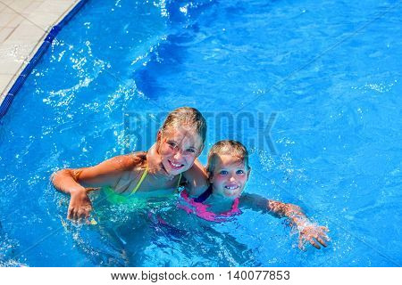 Two nice children hugging and looking up swim in swimming pool. Summer swimming holiday. Outdoor swimming pool. Children activities lifestyle. Blue water in swimming pool.