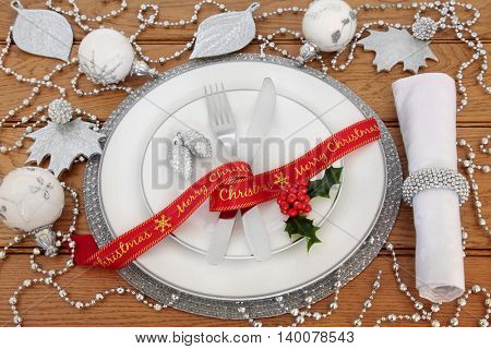 Christmas dinner table setting with porcelain plates, red ribbon, knife and fork, linen serviette,  holly, with silver and white bauble decorations over oak background.