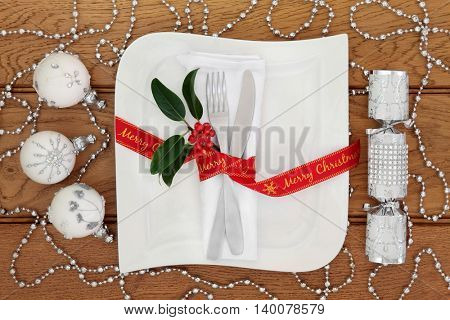Christmas dinner table setting with white porcelain square plate, knife and fork, linen serviette, red merry christmas  ribbon, silver bauble decorations and cracker over oak background.
