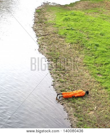 Dummy Of A Man With Orange Jumpsuit On The River Bank