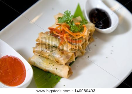 photograph of asian spring roll in plate with chili sauce