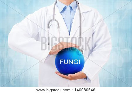 Doctor holding blue crystal ball with fungi sign on medical background.