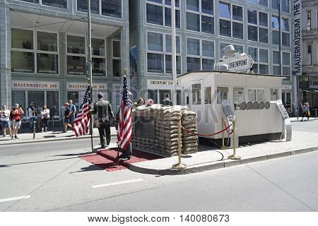 Berlin, Germany- 10 June  2016 : Unidentified young men dress as American soldiers stand in front the check point Charlie remembering the cold war in Berlin Germany