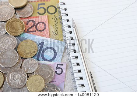 Australian money AUD with notebook selective focus copy space background