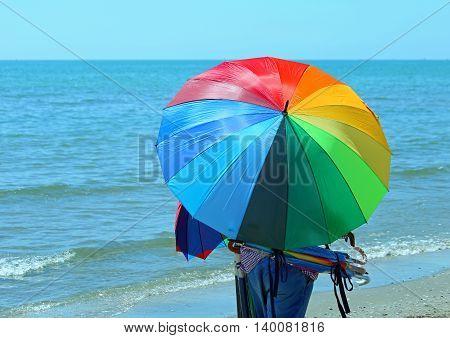 Peddler Of Umbrellas On The Beach In Summer
