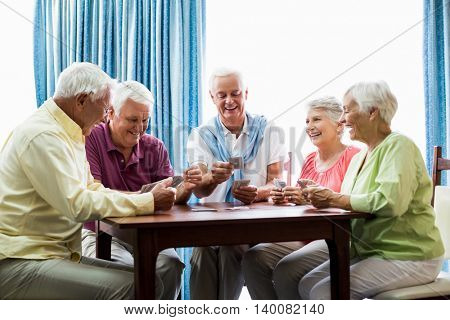 Seniors playing cards together in a retirement home poster