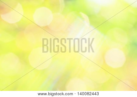 Bright abstract background of green summer garden with yellow patches of sunlight and rays