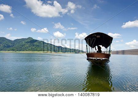 A fishing boat approaches shore area at Khun Dan dam Nakohn Nayok Thailand